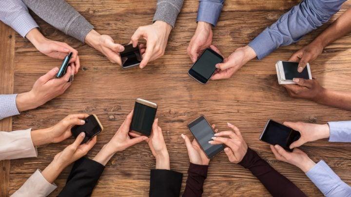 personas con celulares comprando tecnología